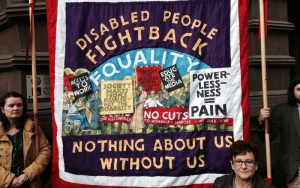 """A protest banner that reads """"Disabled people fight back! Nothing about us without us"""""""