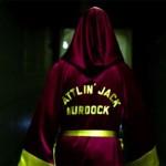 "Jack Murdock walking down a dark hallway, wearing his red satin boxing robe reading ""Battlin' Jack Murdock"" on the back"