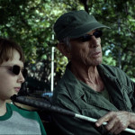 Stick dressed in camo sitting on a park bench with a young Matt Murdock